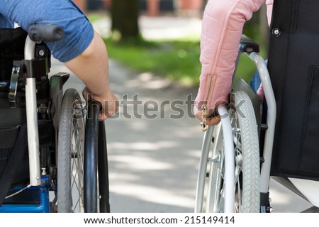 Couple of friends on a wheelchair, horizontal - stock photo