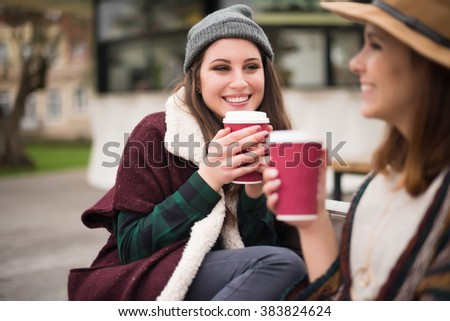 Couple of friends with hot drink on winter