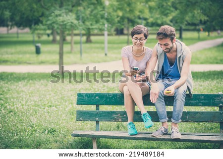 couple of friends young  man and woman using smartphone in the city - stock photo