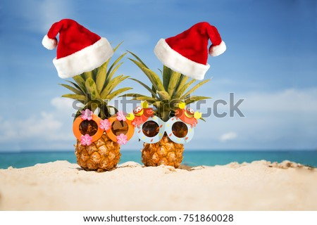 Couple of funny attractive pineapples in children's cheerful sunglasses and New Year's caps on sand against turquoise sea. Christmas and new year concept on a tropical beach. Happy sunny day on beach