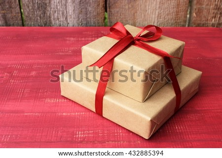 Couple of gift boxes wrapped with simple brown craft paper and decorated with satin ribbon wine red color with a bow. Simple composition in a bright red color Rustic decor elements - stock photo