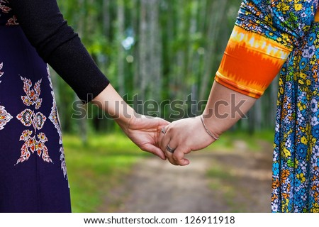 Couple of girlfriends holding by the hands, walking in the forest
