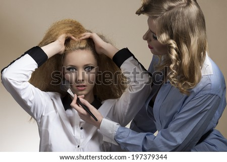 couple of girls posing with creative fashion style, cute hair--style, make-up and sexy shirt applying blush.  - stock photo