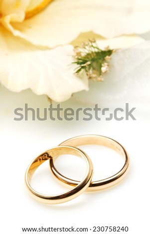 couple of gold wedding rings whit orchid - stock photo