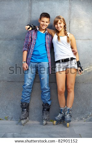 Couple of happy roller skaters looking at camera outside - stock photo