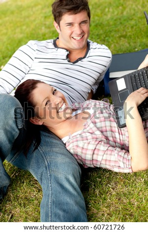 Couple of happy students using a laptop lying on the grass at their campus university smiling at the camera