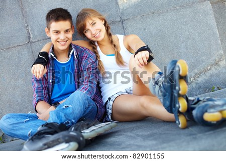 Couple of happy teens on roller skates looking at camera