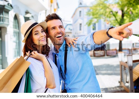 Couple of happy tourists doing shopping in old town - stock photo
