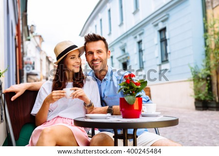 Couple of happy tourists drinking coffee on european city street in outdoors cafe