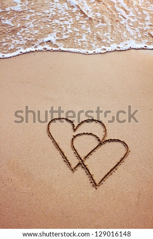 couple of hearts drawn in sand, postcard - stock photo