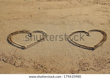 Couple of hearts shape drawn on beach sand