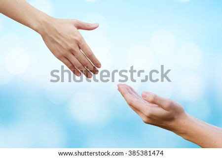 couple of helping/praying hand on blurred colorful sunny sky background,support/aid/love/trust concept.healthcare/therapy/healing conceptual ideal.kindness/compassion/affection:friends and family. - stock photo