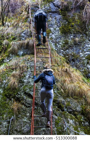 couple of hikers climbing on safety cables in a gorge above the river