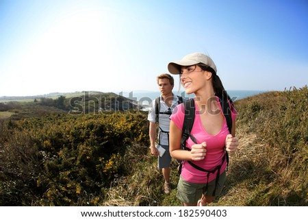 Couple of hikers in country field by the ocean