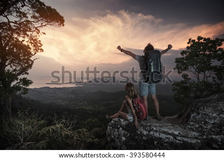 Couple of hikers relaxing on the mountain and watching sunset over the valley - stock photo