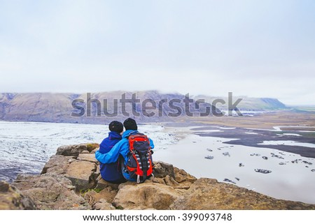 couple of hikers travel in Iceland, two backpackers enjoying view of glacier and mountain landscape
