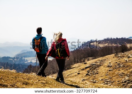 couple of hikers walking in the mountains breathing clean air - stock photo