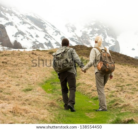 Couple of hikers with backpacks walking in the mountains - stock photo