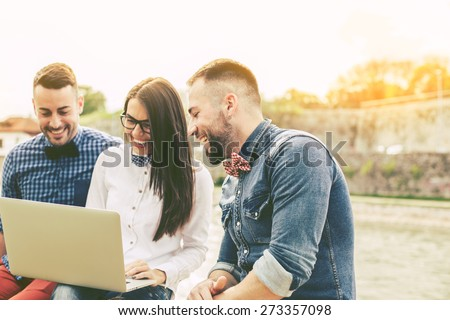 Couple of hipster friends using laptop in the city - stock photo
