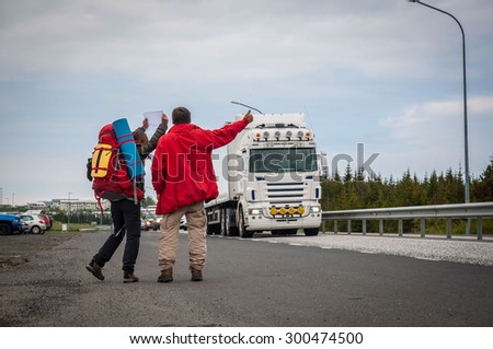 couple of hitch-hikers on the road  - stock photo
