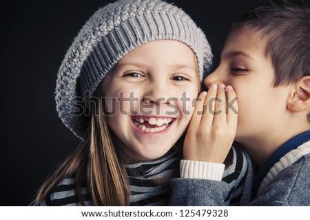 Couple of kids whispering on black background. - stock photo