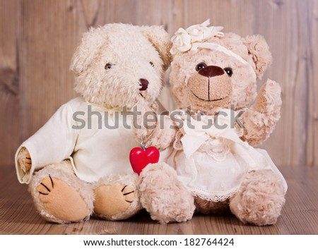 Couple of light brown teddy bear on wooden background - stock photo