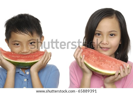 Couple of little kids eating sliced watermelon - stock photo
