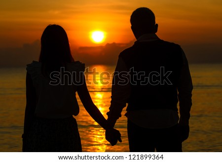 Couple of lover holding hand with sunrise - stock photo