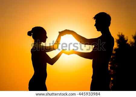 Couple of lover holding hand with sunrise. Girl and boy holding hands at sunset - stock photo