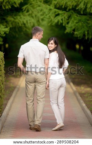 Couple of lovers, attractive young man and woman on date, walking in park, holding hands, smiling girlfriend has turned around, looking back at camera, full length, rear view - stock photo