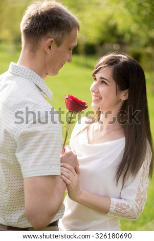 Couple of lovers meeting on a date, looking in each other eyes, young man giving red rose to his beautiful happy smiling brunet girlfriend - stock photo