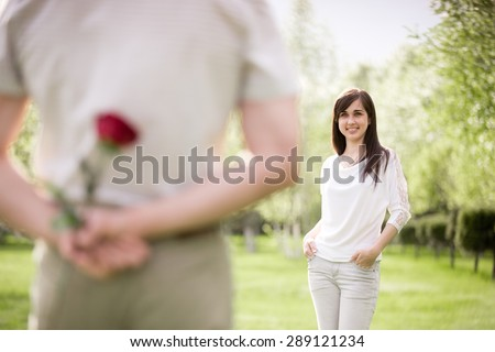 Couple of lovers on a date, focus on smiling young brunet woman in white jersey and jeans looking at young man who is holding red rose behind his back - stock photo