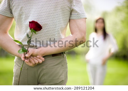 Couple of lovers on a date, focus on young man back who is holding red rose while watching his girlfriend approaching - stock photo