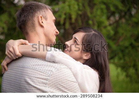 Couple of lovers on a date in park, standing face to face, talking, tenderly embracing, young happy smiling woman playfully hugging and smiling at her boyfriend - stock photo