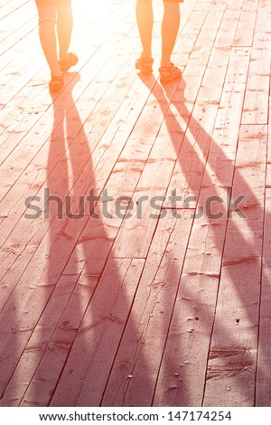 couple of lovers on a wooden bridge at sunset - stock photo