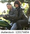Couple of lovers sitting by motorcycle - stock photo