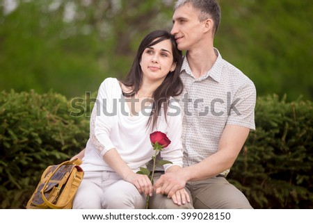 Couple of lovers sitting close on wooden bench in park on a date with dreaming expressions, young man embracing his beautiful brunet girlfriend - stock photo