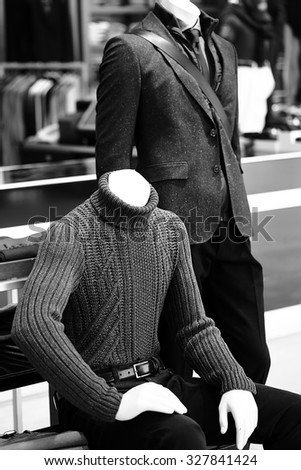 Couple of male fashion mannequins dressed in casual style sitting and standing over dark grey selling floor background black and white, vertical picture  - stock photo