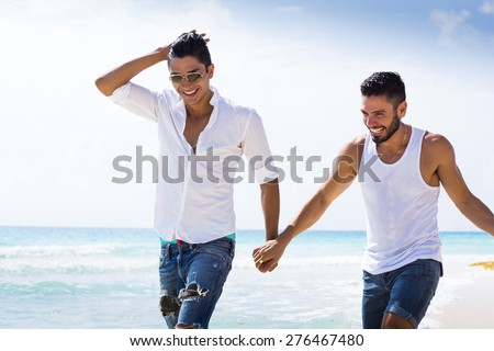 Couple of male friends running at the beach - stock photo