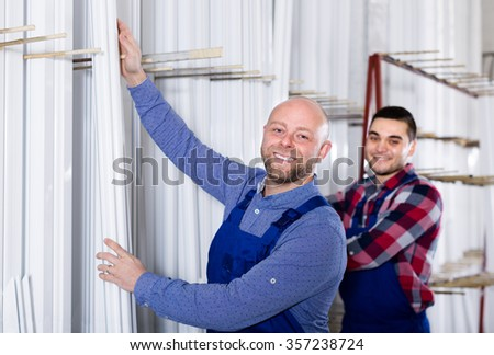 Couple of males  inspecting window frames at factory - stock photo