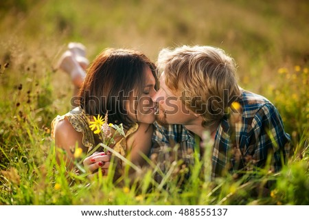 couple of man and woman dressed in country style lying on the field of flowers