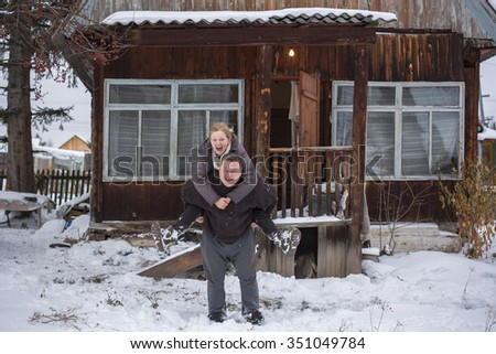 Couple of middle-aged play in the winter near the rural house - stock photo