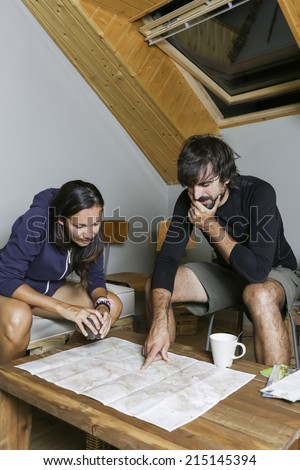couple of mountaineers sitting pointing in a map the planning of the route in a shelter with a cup of coffee - focus on the mountaineers - stock photo