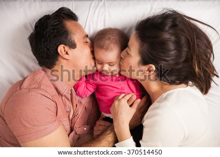Couple of new parents lying in a bed with her baby girl and kissing her both at the same time  - stock photo