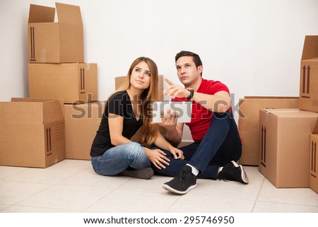 Couple of newlyweds looking at some empty space on their new home and visualizing their furniture and decorations