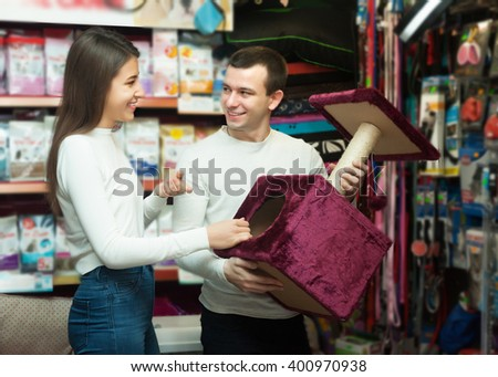 Couple of ordinary customers buying kennel for pet in store - stock photo