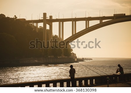 Couple of people fishing at Douro river. - stock photo