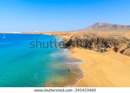 Couple of people in turquoise ocean water on Papagayo beach, Lanzarote, Canary Islands, Spain - stock photo