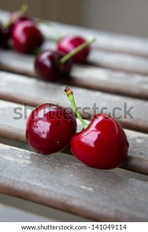 Couple of red cherries on a wooden surface closeup