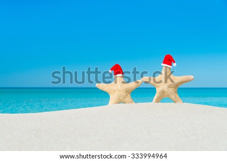 Couple of Sea-stars in red Santa hats walking at tropical beach. New Year's day or Christmas in hot countries vacation concept - stock photo